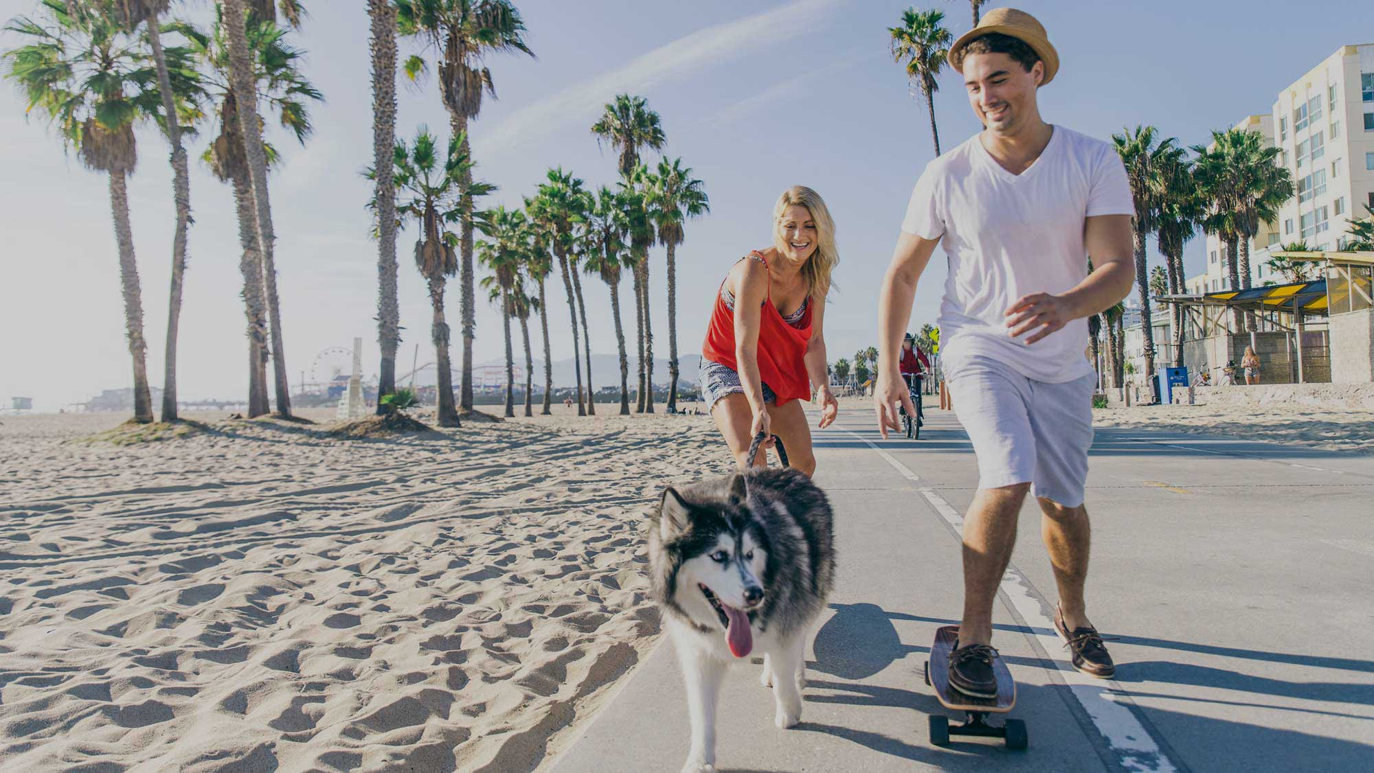 Couple and dog cruising the strand